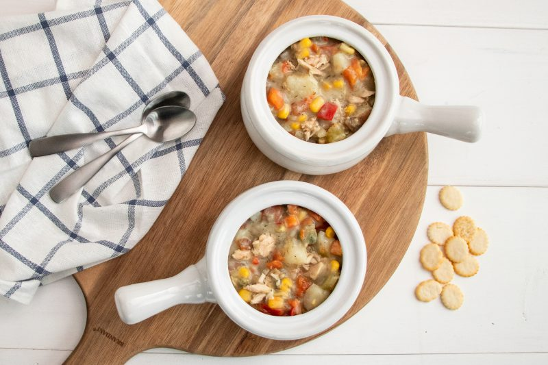 2 bowls of Hearty Pacific Chowder on a wooden circle board