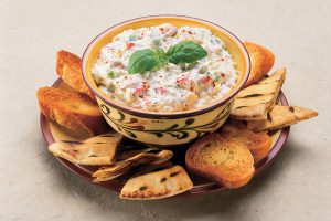 A bowl of Hot Crab and Artichoke Dip with bread and crackers