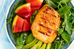 A plate of grilled watermelon, avocado slices, mint leaves and thai chili tuna