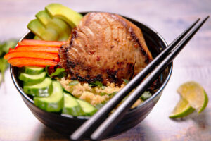 A quinoa bowl topped with a yellowfin tuna steak, cucumbers, red pepper, avovado, cilantro and lime juice.