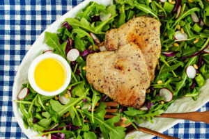 2 Black Pepper Yellowfin Tuna Steaks on a bed of arugula salad, dressing on the side
