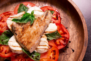 Naked Yellowfin Tuna Steak on a Caprese Salad on a wooden plate